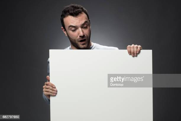 Young man showing empty white billboard
