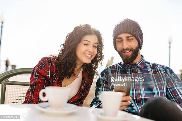 Young man showing his cell phone to girlfriend at a street cafe