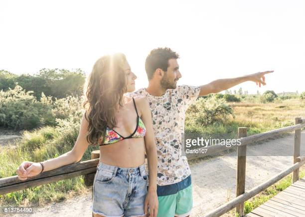 Young man showing the horizon to his girlfriend in Tuscan countryside