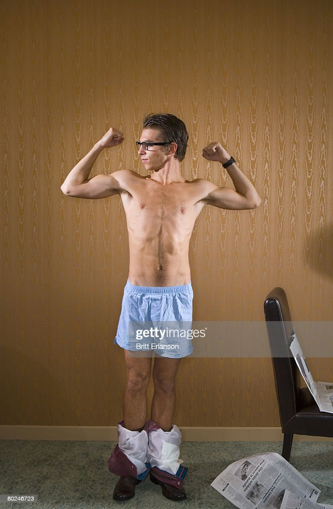 Young man shows flexes arm muscles.