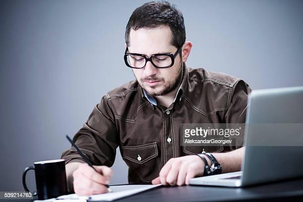 Junger Mann, die Unterzeichnung Vertrag und arbeiten auf seinem Computer