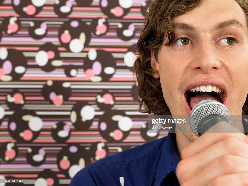 Young man singing into microphone, close-up : Stock Photo