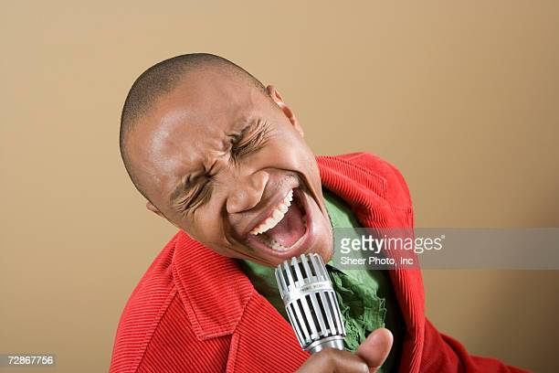Young man singing into microphone, mouth open, close-up