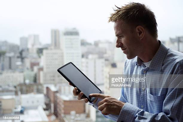 Young Man Siting Using Tablet Computer Above City Skyline