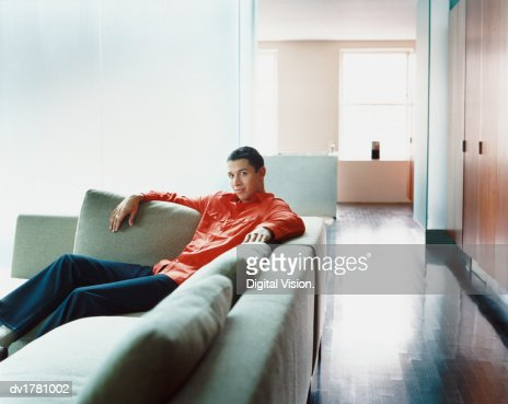 Young Man Sits on a Comfortable Sofa in His Apartment : Stock Photo