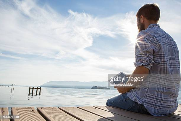 Young man sits on jetty above lake, uses digital tablet