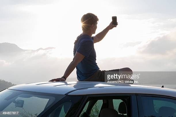 Young man sits on roof of car, takes phone pic