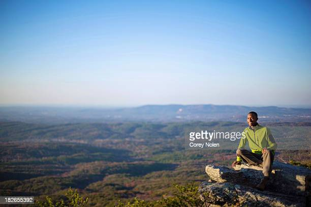 A young man sits on the ledge of a rock overlook on top of Mount Cheaha.