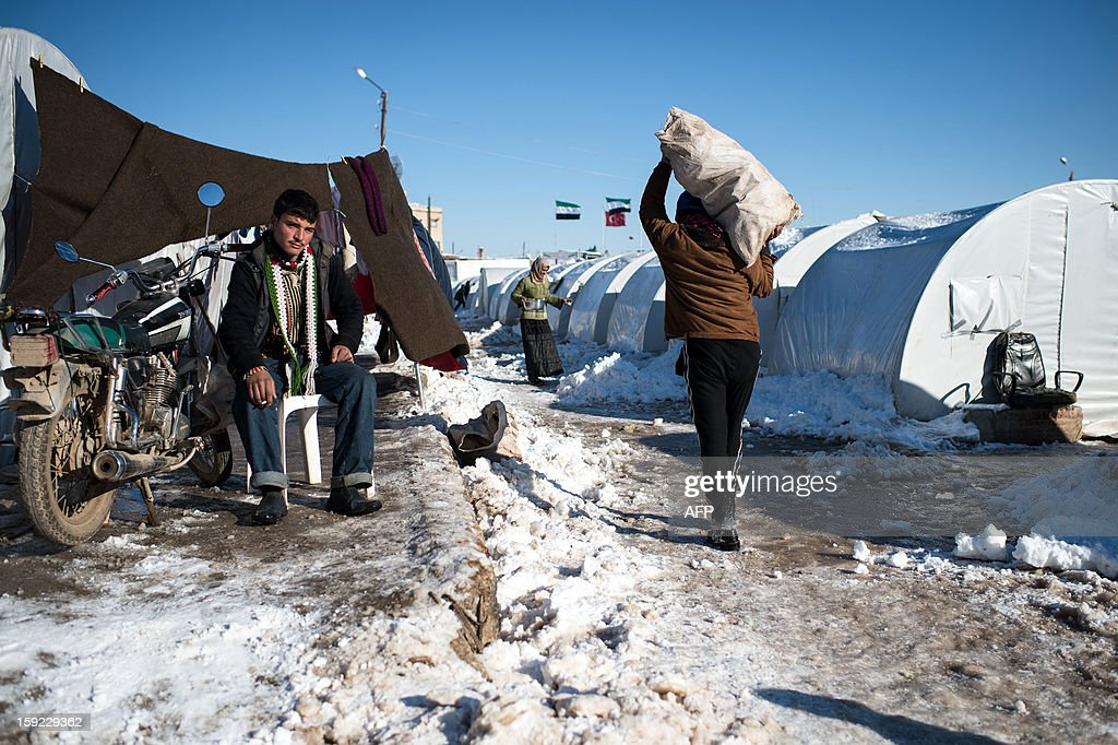 A young man sits smoking in a Syrian refugees camp in Azaz, near the Turkish border, on January 10, 2013 after snow falls. Snow carpeted Syria's war-torn cities but sparked no let-up in the fighting, instead heaping fresh misery on a civilian population already enduring a chronic shortage of heating fuel and daily power cuts.