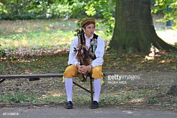 A young man sits with his bagpipes on a bench during the oldest folklore festival of Europe in Straznice south Moravia 80 km southeast from Brno...