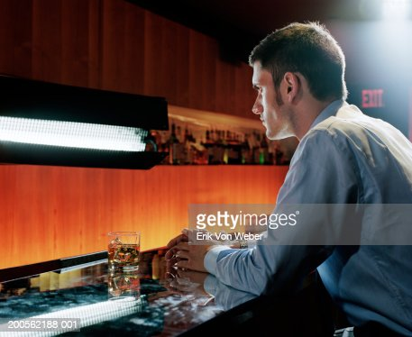 Young man sitting at bar, side view : Stock Photo