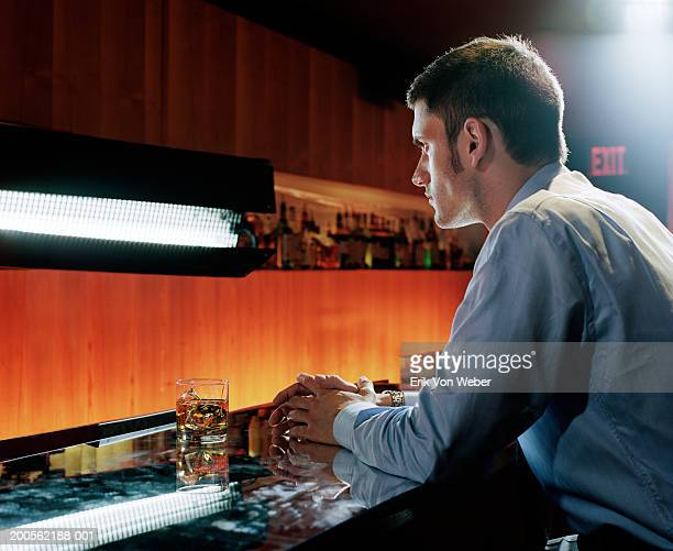 Young man sitting at bar, side view