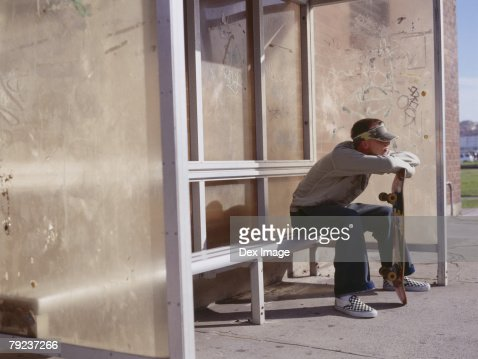Young man sitting at bus stand holding a skateboard : Stock Photo