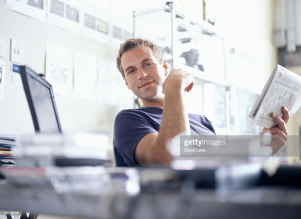 Young man sitting at desk holding newspaper, portrait : Stock Photo