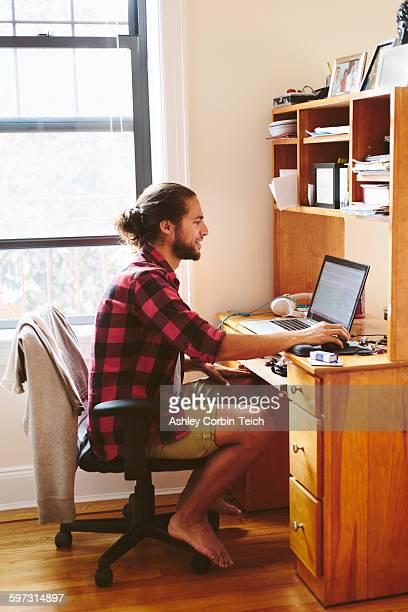 Young man sitting at desk, using laptop