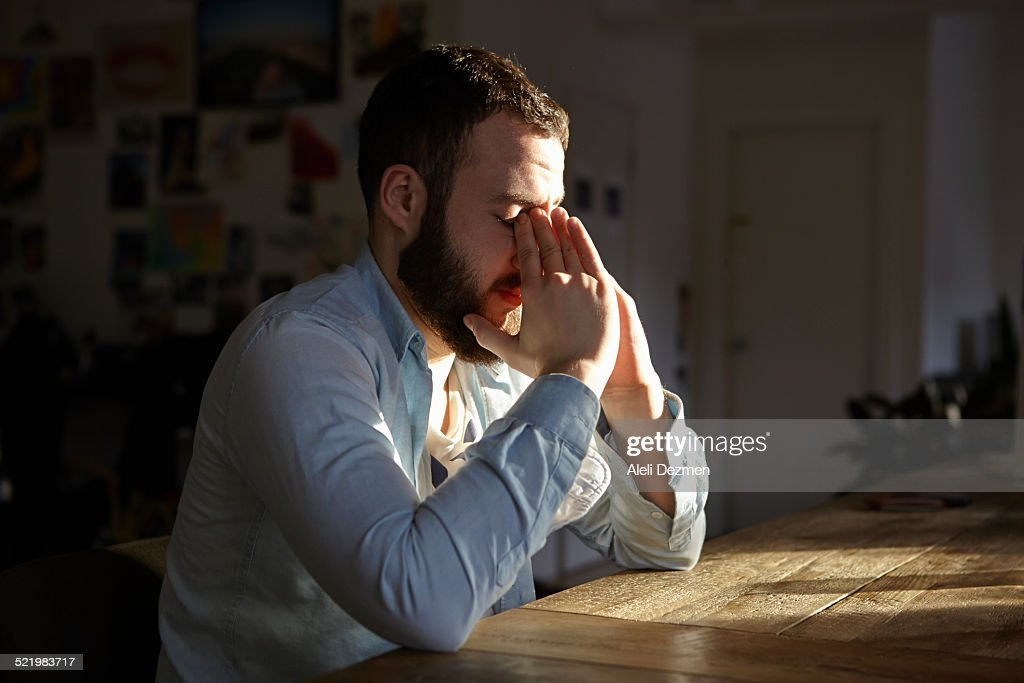 Young man sitting at kitchen table with hands on face : Stockfoto