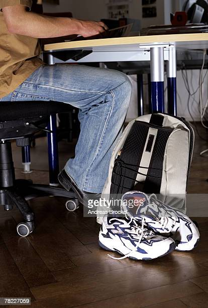 Young man sitting at office desk, sports bag and trainers next to him, view from below