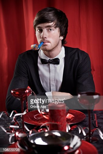 Young Man Sitting at Table Blowing Party Horn Blower : Stock Photo