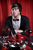 Young Man Sitting at Table Blowing Party Horn Blower
