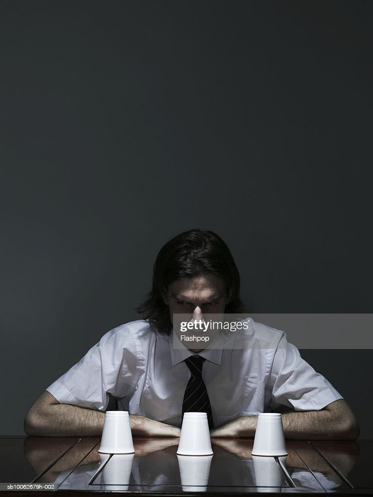 Young man sitting at table, looking at disposable cup : Stock Photo