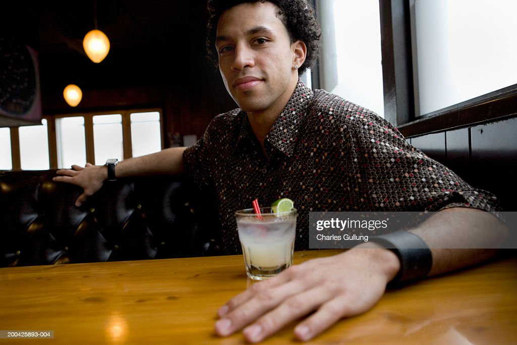 Young man sitting at table with cocktail, portrait : Stock Photo
