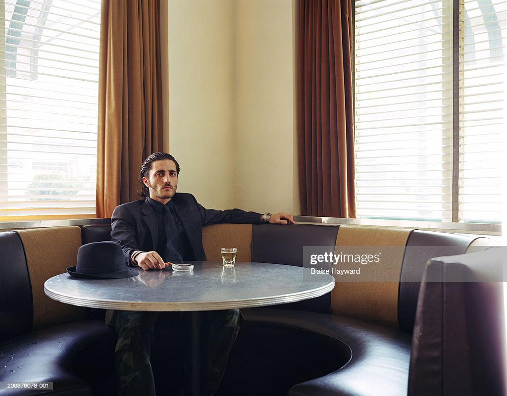 Young man sitting at table with drink and cigarette, portrait : Stock Photo