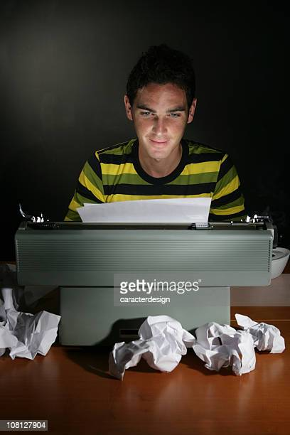 Young Man Sitting at Typewriter with Balls of Paper Everywhere