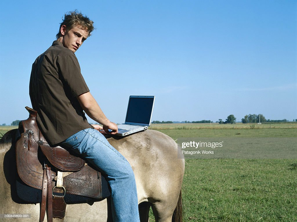 Young man sitting backwards on horse, using laptop, side view