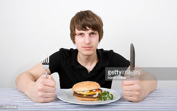 Young man sitting before burger and holding knife and fork