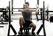 Young man sitting behind weight in gym