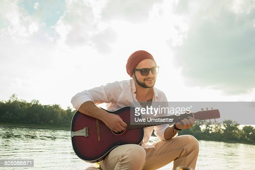 Young man sitting by lake playing guitar