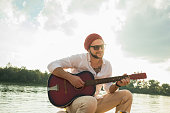 Young man sitting by lake playing guitar