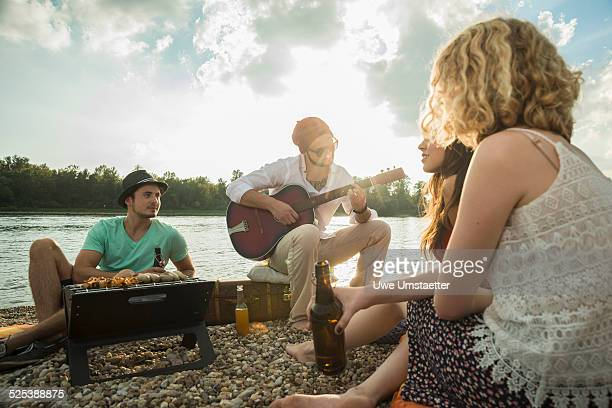 Young man sitting by lake with friends playing guitar