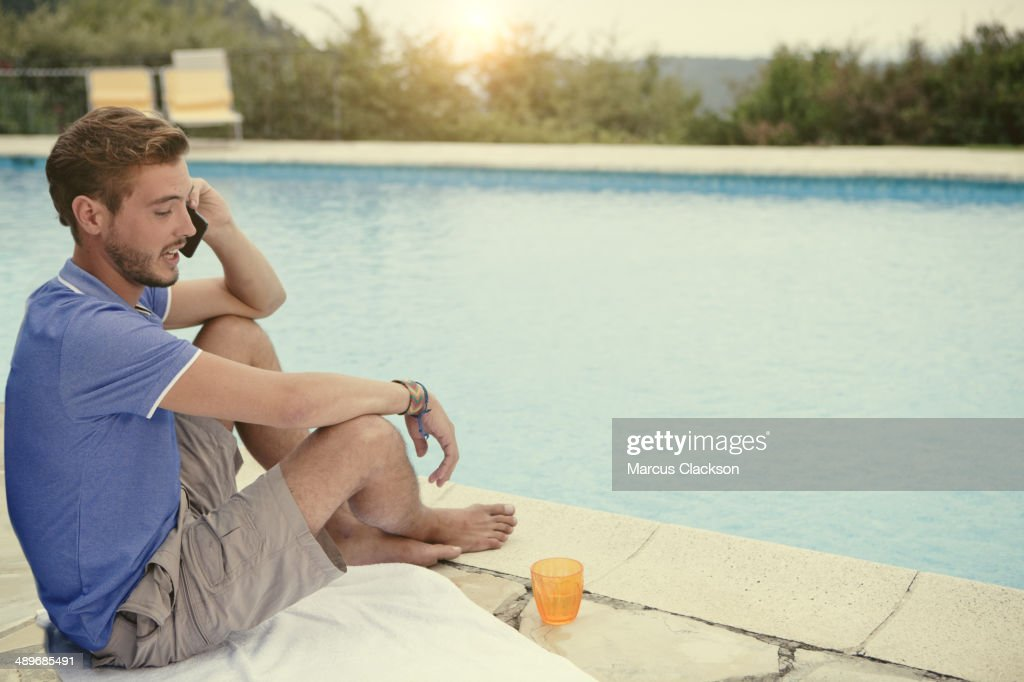 Young man sitting by the pool on his phone