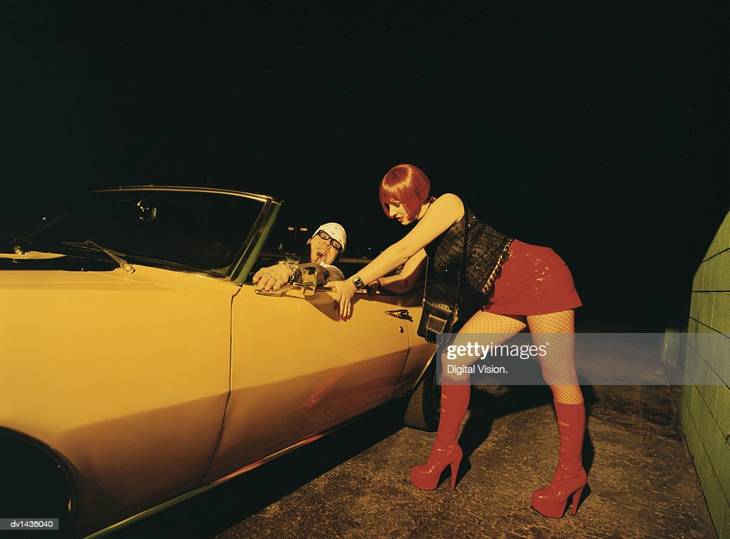 Young Man Sitting in a Car Talking to a Prostitute at Night