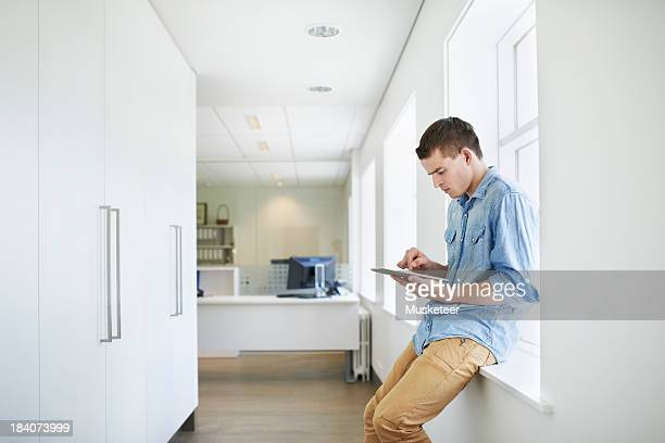 Young man sitting in a hallway using a tablet