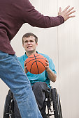 Disabled man sitting in a wheelchair and playing basketball with another man
