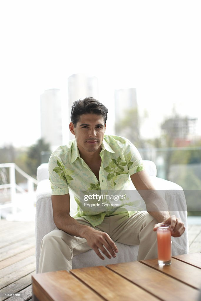 Young man sitting in armchair outdoors, portrait : Stock Photo