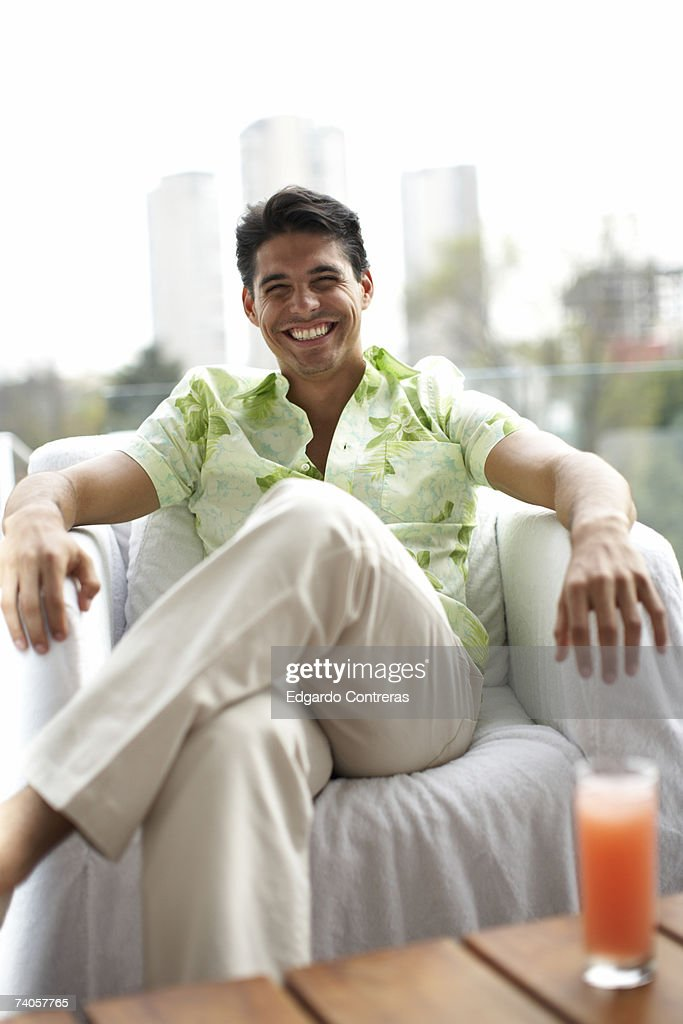 Young man sitting in armchair outdoors, smiling, portrait : Stock Photo