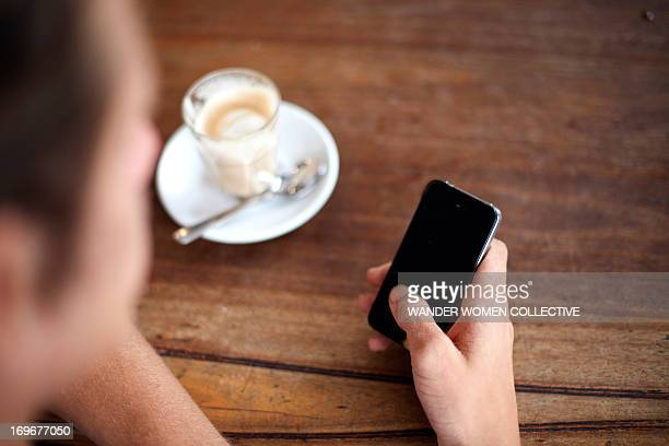 Young man sitting in cafe texting SMS mobile phone