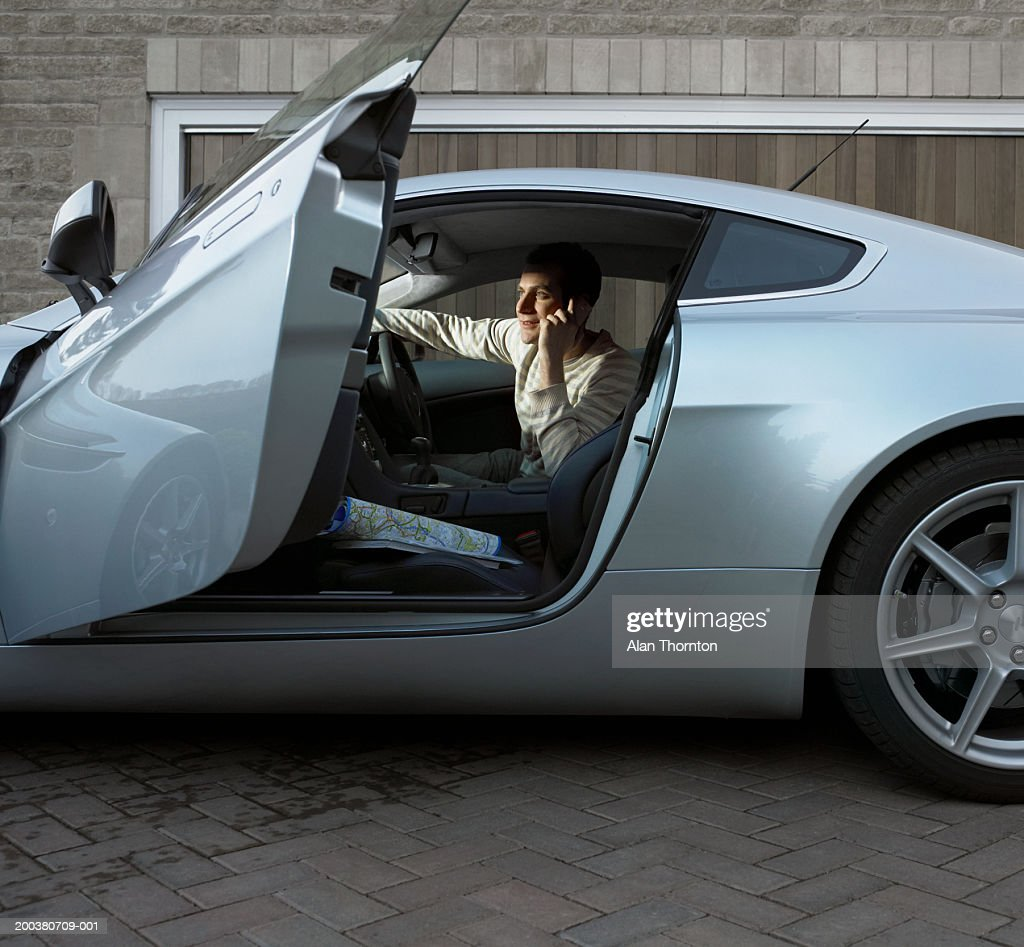 Young man sitting in car, using mobile phone, side view : Stock Photo