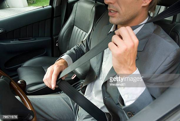 'Young man sitting in car, using seat belt'