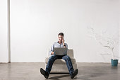 Young man sitting in empty office room, using cell phone and notebook PC