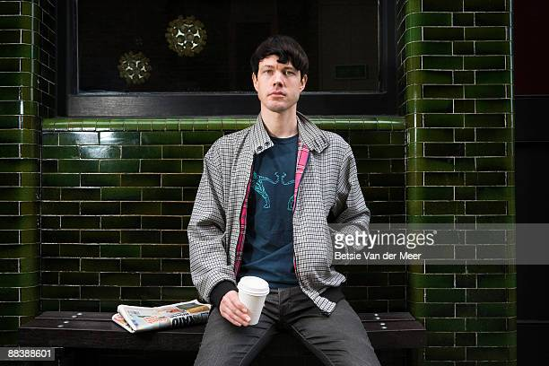 Young man sitting in front of cafe.
