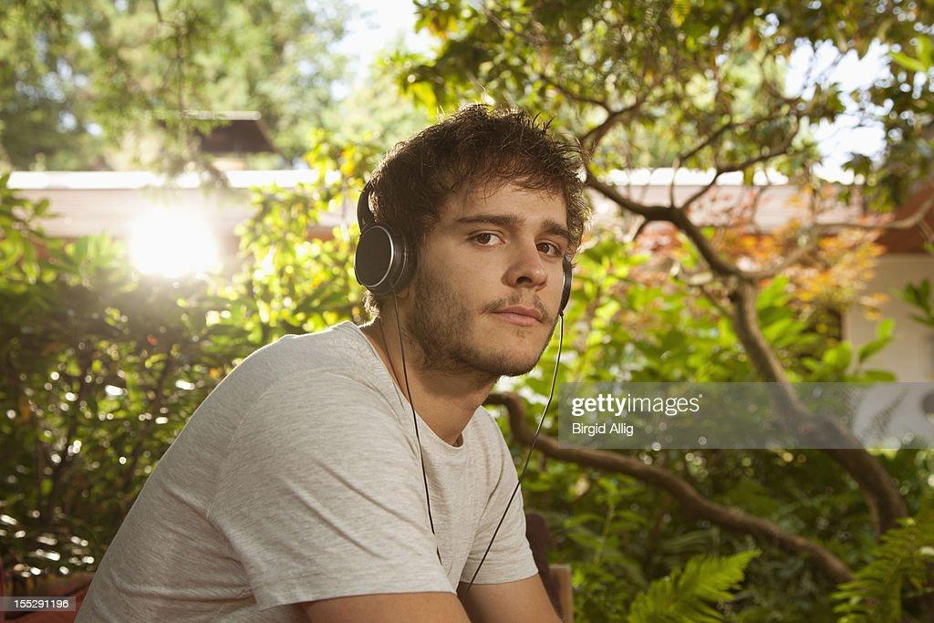 Young man sitting in garden with earphones : Stock Photo