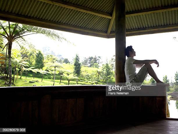 Young man sitting in gazebo, side view