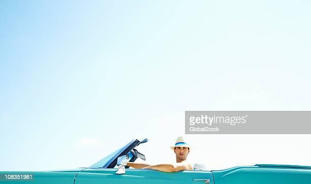Jeune homme assis dans sa voiture décapotable-copyspace