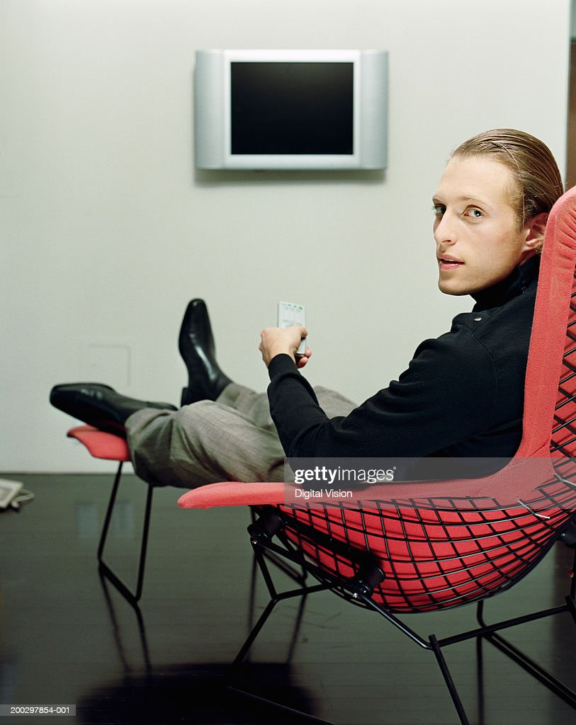 Young man sitting in modern chair holding remote control for Modern sitting chairs