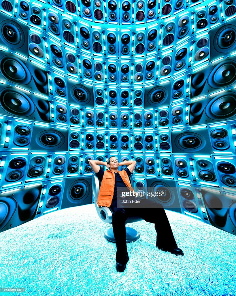Young man sitting in room full of speakers (Digital Composite) : Stock Photo