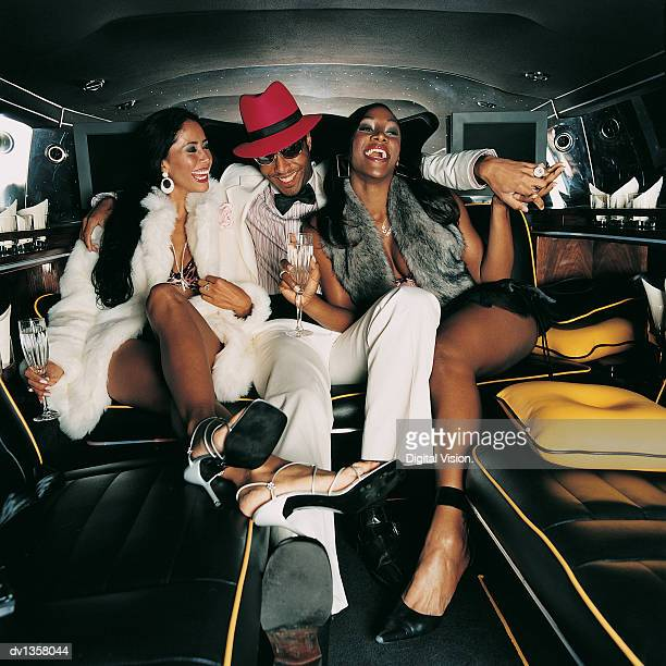 Young Man Sitting in the Back Seat of a Limousine With His Arms Around Two Young Women